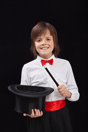 magician: Happy magician boy on black background - with magic wand and hat