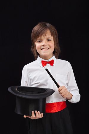 mago: Mago del muchacho feliz en el fondo negro - con la varita m�gica y el sombrero Foto de archivo