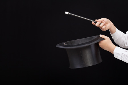 illusionist: Magician hands with magic hat and wand pointing to copy space on the left Stock Photo