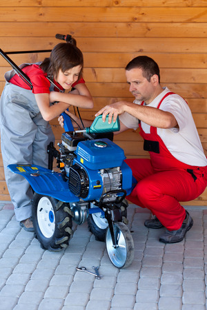 servicing: Man and boy servicing a small tiller machine - adding oil Stock Photo