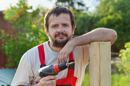 worker man: Handyman working in the yard - leaning on a fence support