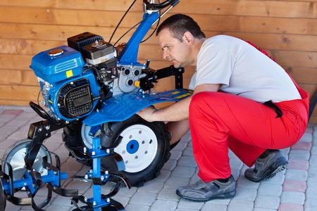 MOTORIZADO: la agricultura a pequeña escala y sostenibilidad - hombre que controla el timón pequeña máquina motorizada