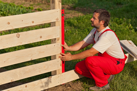 handy man: Man building wooden fence - checking regularly with a spirit level