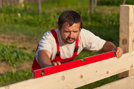 spirit level: Worker building wooden fence - checking with spirit level