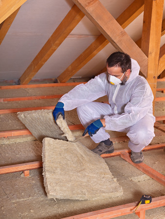 rockwool: Worker cutting mineral wool panel installing thermal insulation on a building