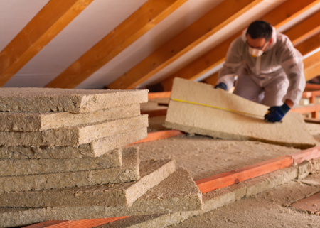 planck: Thermal insulation of a building - mineral wool panels stack with man measuring in the background
