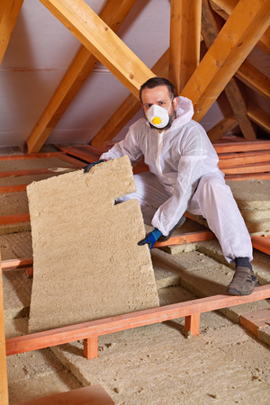 planck: Man installing thermal isnulation with mineral whool panels under the roof