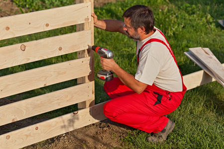 Man building a wooden fence - fastening the boards with screws 스톡 콘텐츠