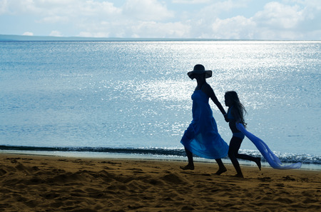 Woman and little girl silhouette on the beach at sunrise - strong backlight, copyspace photo
