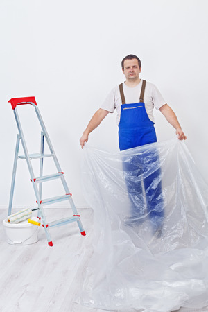 floor covering: Worker preparing a room to repaint - covering the floor with thin plastic foil Stock Photo