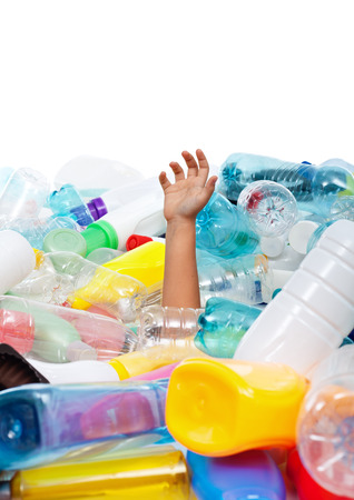 Child hand sticking out from plastic bottles garbage - environmental disaster concept, copyspace