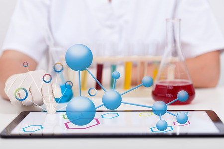 documenting: Conducting chemical experiments and documenting it on tablet computer - closeup