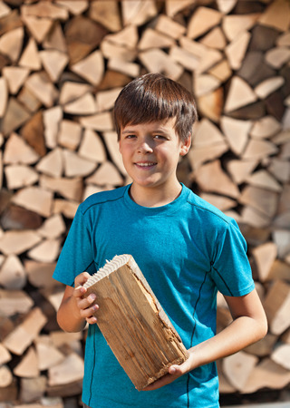 Boy stacking firewood - holding a piece and posing for the camera Stock Photo