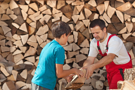 Boy helping his father stacking the firewood - handing him the pieces Stock Photo