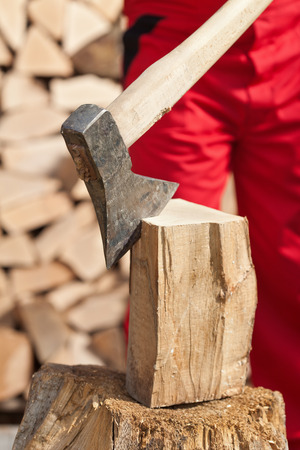 Detail of man chopping firewood - closeup on wood block and axe