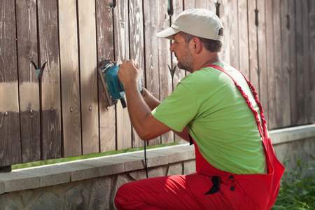 sanding: Worker sanding away old paint from a wooden fence using power tool