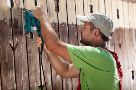 Worker with vibrating sander removing old paint from wooden fence Stock Photo