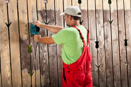 paint tool: Worker scraping old cracked paint from wooden fence with power tool - a vibrating sander
