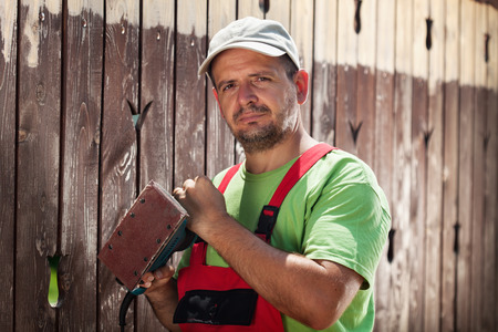 vibrating: Worker about to scrape away the old paint from a wooden fence - standing with a vibrating sander