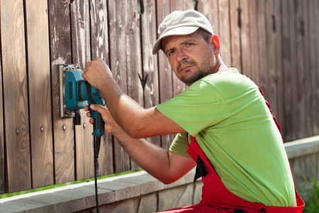 power tool: Worker polishing old wooden fence with power tool - a vibrating sander, scraping the cracked paint