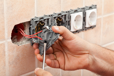 Electrician hands tighten electrical wires in wall fixture or socket using a screw driver - closeup