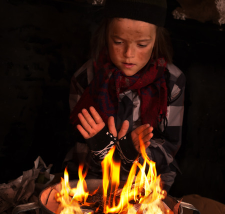 Young homeless boy warming by the newspapers fire made in a large tin pot - focus on the fire