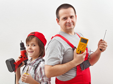 Electrician father and helping son ready for work - posing with tools in front of white wall photo