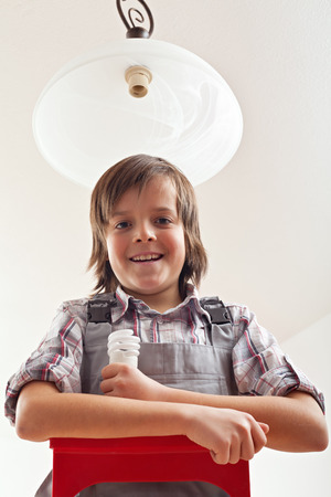 Boy changing lightbulb in ceiling lamp - smiling on the top of ladder holding a fluorescent bulb photo