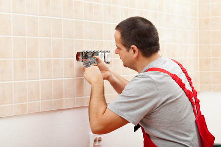 wall socket: Electrician installing electrical wall fixture - fastening the wires in the receptacle