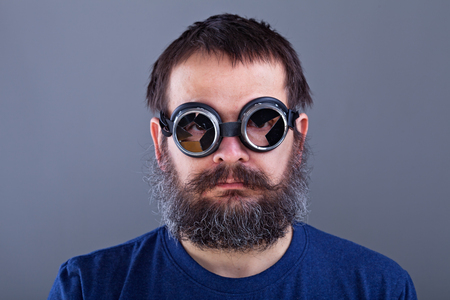 matted: Weird guy with matted hair and large beard wearing broken welding goggles Stock Photo