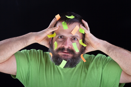 Stressed man with large beard worried about forgetting things - covered with post-it stickers