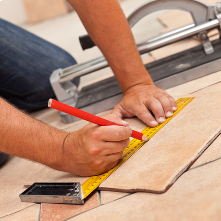 Laying ceramic floor tiles - man kneeling and marking tile to be cut, closeup on hands