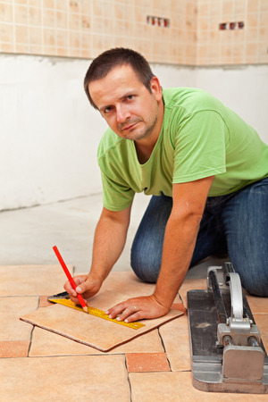 Man laying ceramic floor tiles - measuring and cutting one piece knealing with the tools on the concrete floor