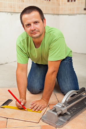 Man laying ceramic floor tiles in a new building - marking one tile for cutting to dimensions