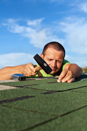 Man fastening bitumen roof shingles with nails and hammer - low angle view, focus on hand Stock Photo