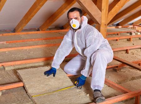 Man installeren thermische isolatiepanelen tussen houten steiger