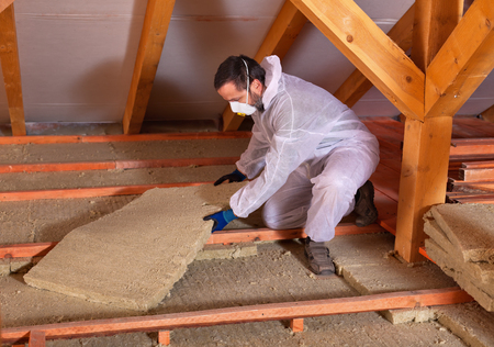 rockwool: Man laying thermal insulation - placing rockwool panels to form layers