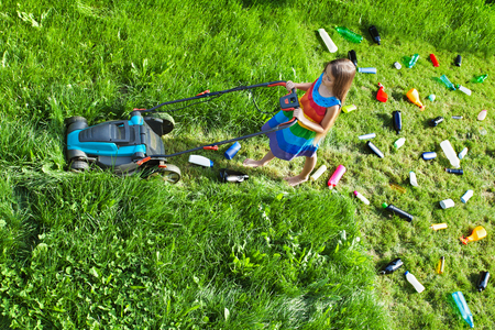 Young girl pushing a lawnmower cutting grass and leaving plastic litter behind - top view photo