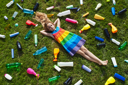 Sad little girl lying on the garbage filled grass - plastic pollution concept photo