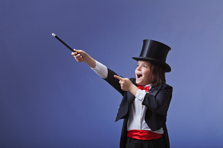 Young magician performing with a magic wand pointing to copy space