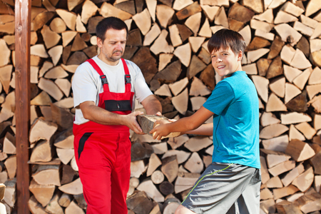 Teenage boy helping father stack the firewood - handing him the wooden blocks photo