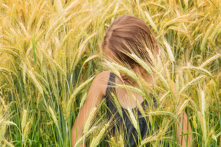 Little girl submerged under the spikes of a ripening grain field looking down photo
