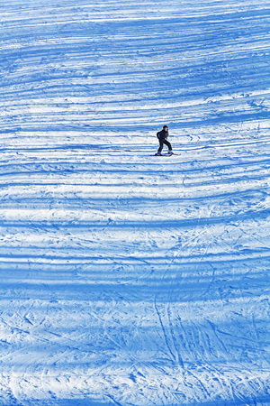Girl skiing alone on the late afternoon snowy slopes with transversal shadows from neighbouring trees