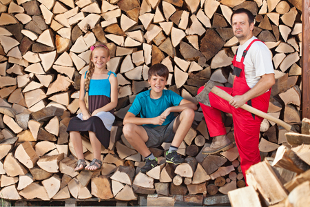 Father and kids taking a break from chopping and stacking firewood into a wood shed photo
