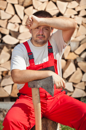 Tired worker done chopping and stacking the firewood - wiping forehead with one arm and resting the other on axe photo
