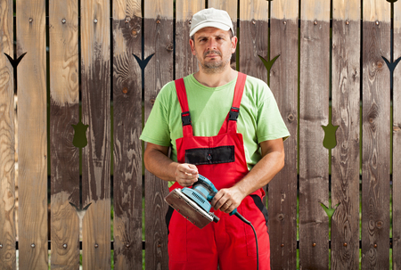 Worker man scraping old cracked paint from fence with an electric vibrating sander photo