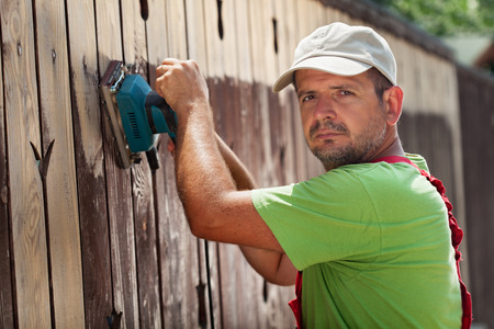 Man removing old cracked paint from a fence using an electic vibrating sander - working in sunshine photo