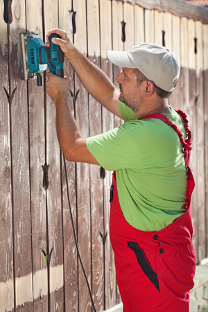 Man renewing a wooden fence - sanding away the old paint coat photo
