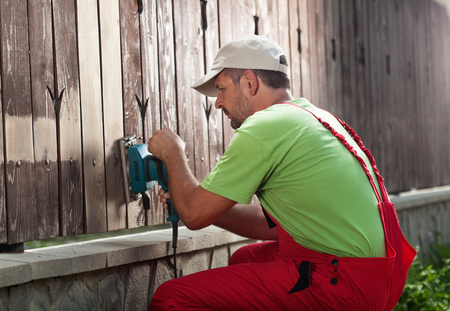 Worker removing old paint from fence using an electric hand tool photo