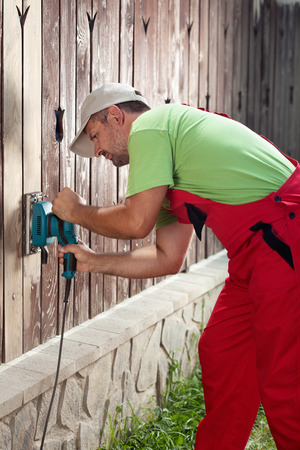 Man refurbishing old wooden fence - removing cracked paint layer with electric vibrating sander machine Stock Photo